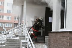 Firefighter enters to smoking door Stock Images
