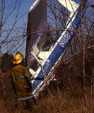 Firefighter examines a plane crash in wooded area royalty free stock image
