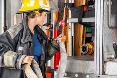 Firefighter Examining Water Hose By Truck. Female firefighter examining water hose by truck at fire station royalty free stock image