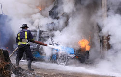 Firefighter extinguish a burning car Royalty Free Stock Photography