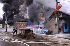 Firefighter extinguish a burning car Royalty Free Stock Photos
