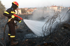 Firefighter extinguish fire in a field by water flooding Stock Photography