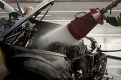 Firefighter extinguishes a burning car engine Royalty Free Stock Image