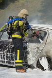Firefighter extinguishes car fire. With foam. Wearing breathing apparatus Royalty Free Stock Images