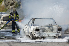 Firefighter extinguishes car fire. With foam. Wearing breathing apparatus Stock Photography