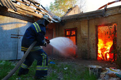 Firefighter extinguishes fire. With water Royalty Free Stock Images