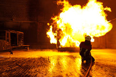 Firefighter extinguishes a fire Royalty Free Stock Image