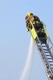 Firefighter extinguishes fire. Fireman puts out fire royalty free stock photo