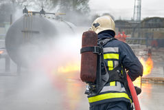 Firefighter extinguishing tank fire. Firefighter in protective clothing, with helmet and oxygen tank extinguishing tank fire with a hose and water jet in an Royalty Free Stock Photography
