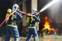 Firefighter fighting For A Fire Attack, During A Training Exerci Royalty Free Stock Photos
