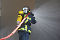 Firefighter fighting For A Fire Attack, During A Training Exerci Royalty Free Stock Image