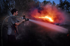 Firefighter fights large wildfire. CHOF ASHKELON, ISR - MAY 30:Firefighter fights large wildfire on May30 2008.More than 80 percent of all wildfires are started Royalty Free Stock Images