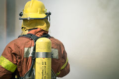 Firefighter fire fighting suround with dark smoke Stock Image