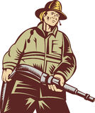 Firefighter fireman with fire hose. Illustration of a Firefighter carrying a hose viewed from a low angle done in woodcut style Royalty Free Stock Photography