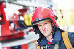 Firefighter fireman. Firefighter in uniform in front of fire engine machine and fireman team Royalty Free Stock Photo