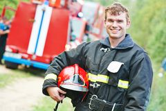 Firefighter fireman. Young smiling fireman firefighter in uniform in front of fire engine machine Stock Photos