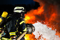Firefighter - Firemen extinguishing a large blaze. They are standing with protective wear in front of wall of fire Royalty Free Stock Photos