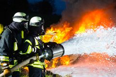 Firefighter - Firemen extinguishing a large blaze. They are standing with protective wear in front of wall of fire royalty free stock images