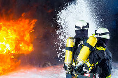 Firefighter - Firemen extinguishing a large blaze. They are standing with protective wear in front of wall of fire Stock Photos