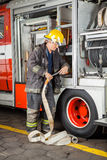 Firefighter Fixing Hose In Truck Stock Images