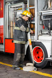 Firefighter Fixing Water Hose In Truck Stock Photos