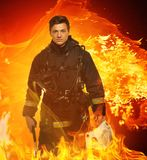 Firefighter in a flame. Firefighter with helmet and axe in a flame Stock Images