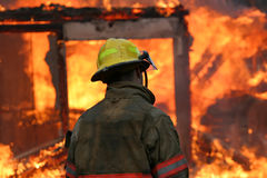 Firefighter in Flames. Single fireman standing in front of a fully engulfed residential structure fire Stock Photo
