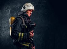 Firefighter in full protective equipment holding an oxygen mask and looking at a camera. Brutal firefighter in uniform and safety helmet holding an oxygen mask royalty free stock photos
