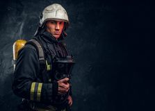 Firefighter in full protective equipment holding an oxygen mask and looking at a camera. Studio photo against a dark textured wall stock image