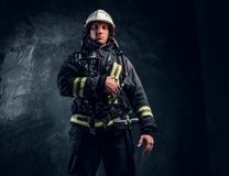 Firefighter in full protective equipment holding an oxygen mask and looking at a camera. Studio photo against a dark textured wall stock images
