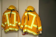 Firefighter gear. Firefighter jackets and helmets hanging in the fire station Stock Photos