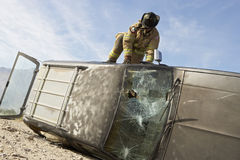 Firefighter Getting Into Crashed Car Royalty Free Stock Image