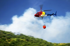 Firefighter helicopter. In action flying over a fire in the mountains Stock Photography
