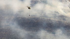 A firefighter helicopter rushes to help put out a wildfire royalty free stock photography