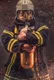 Firefighter in helmet and mask holds oxygen tanks. Firefighter in helmet and mask holds oxygen tanks in a sparks royalty free stock photo