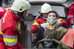 Firefighter in action. A firefighter holding wounded young man in car accident. Photo taken during an exercise Stock Images