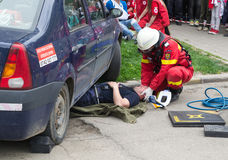 Firefighter helping victim. Public simulation of car accident. Firefighter holding head of victim incarcerated under the car Royalty Free Stock Image