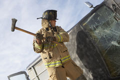Firefighter Hitting Crashed Car With Axe royalty free stock photos