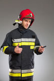 Firefighter holding cell phone and showing thumb up. Royalty Free Stock Photos