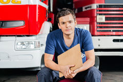 Firefighter Holding Clipboard While Sitting Stock Image