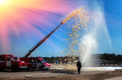 Firefighter holding a fire hose with water pressure, fire fighti Stock Photos