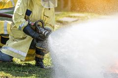 Firefighter holding high pressure fire hose nozzle. stock photos