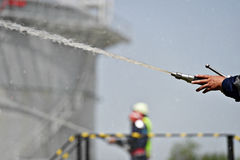 Firefighter holding high pressure water hose Stock Images
