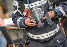 Firefighter holding oxygen or gas mask. Close up on firefighter man holding oxygen or gas mask in his hands stock photography