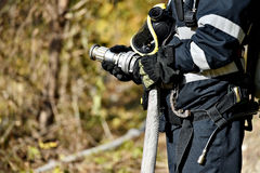 Firefighter holding water hose Stock Photo
