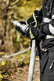 Firefighter holding water hose Stock Images