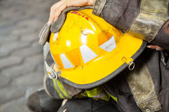 Firefighter Holding Yellow Helmet At Fire Station Stock Photo