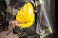 Firefighter Holding Yellow Helmet. Midsection side view of female firefighter holding yellow helmet at fire station stock image