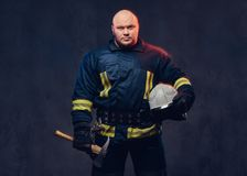 Firefighter holds the axe. Studio portrait of a firefighter in uniform holds the axe Stock Image