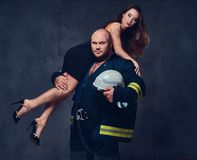 Firefighter holds a woman. Brutal firefighter holds and hot brunette female on his shoulder stock photos